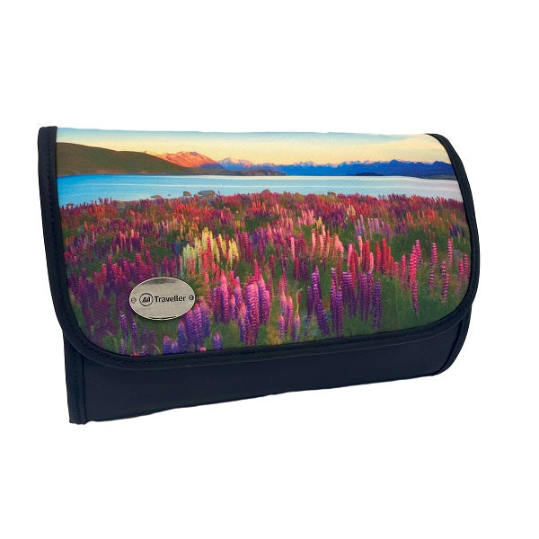 A rectangular cosmetic bag with which secures with a Velcro strip across the top. The front of the bag displays a beautiful scene of pink and purple lupins, with New Zealand's spectacular mountain ranges in the background, under a blue sky with wispy clouds. The front left corner hosts a silver badge with the AA Traveller logo. The back and sides are black, with a black Velcro strip and unfolds into 4 compartments.