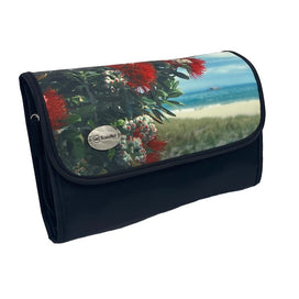 A rectangular cosmetic bag with which secures with a Velcro strip across the top. The front of the bag displays a Kiwi summer scene of blooming Pohutukawa tree with red flowers surrounded by green leaves, and a hot Summer's day beach in the background with clear waters, white sand and a blue sky with wispy clouds. The front left corner hosts a silver badge with the AA Traveller logo. The back and sides are black, with a black Velcro strip and unfolds into 4 compartments.