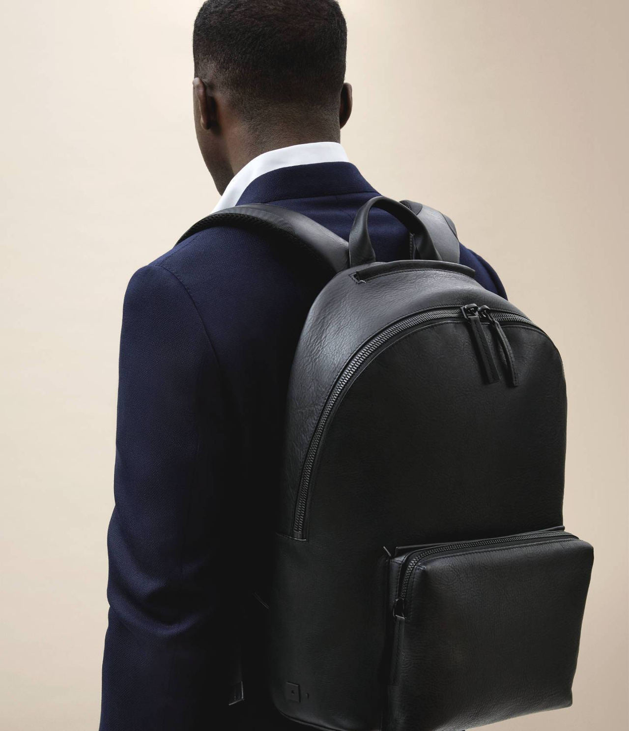 Navy suit and black leather backpack