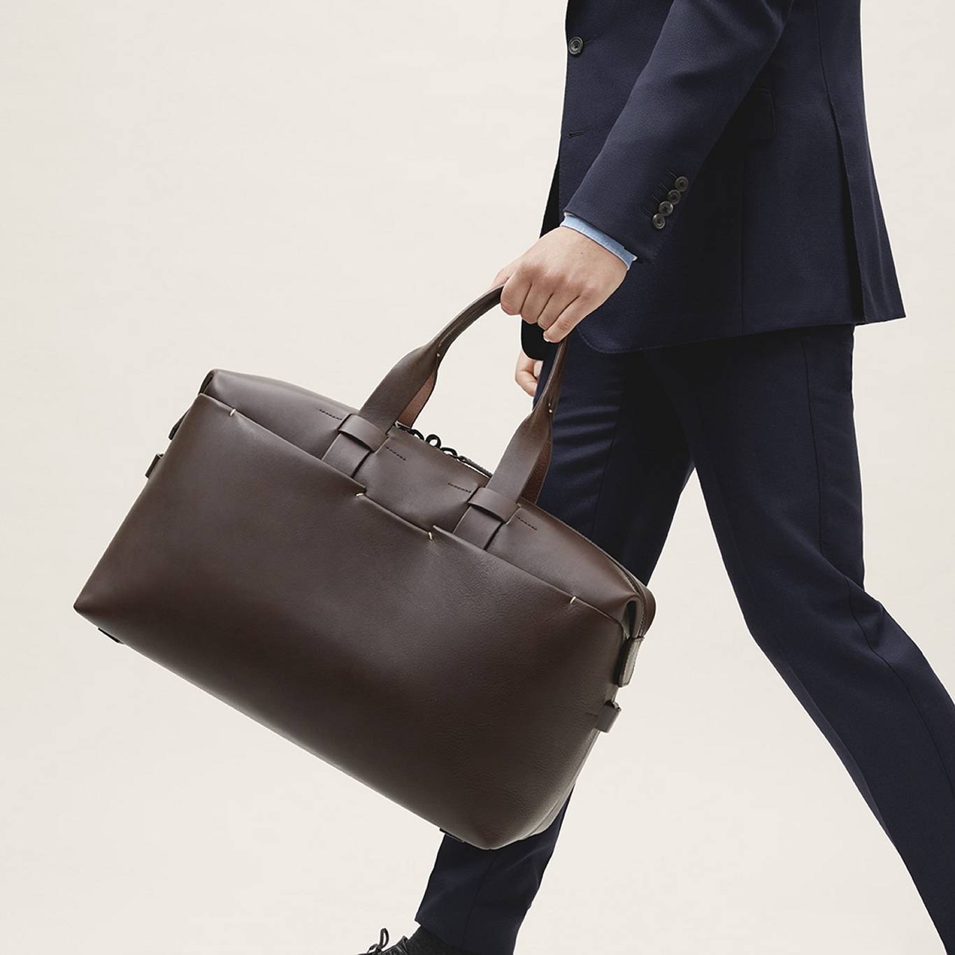 Man with navy blue suit carrying Troubadour's brown leather weekend bag
