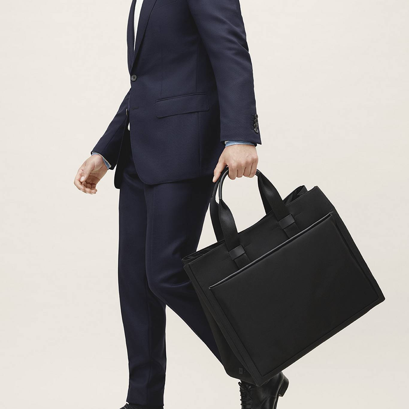 Navy suit and black tote bag