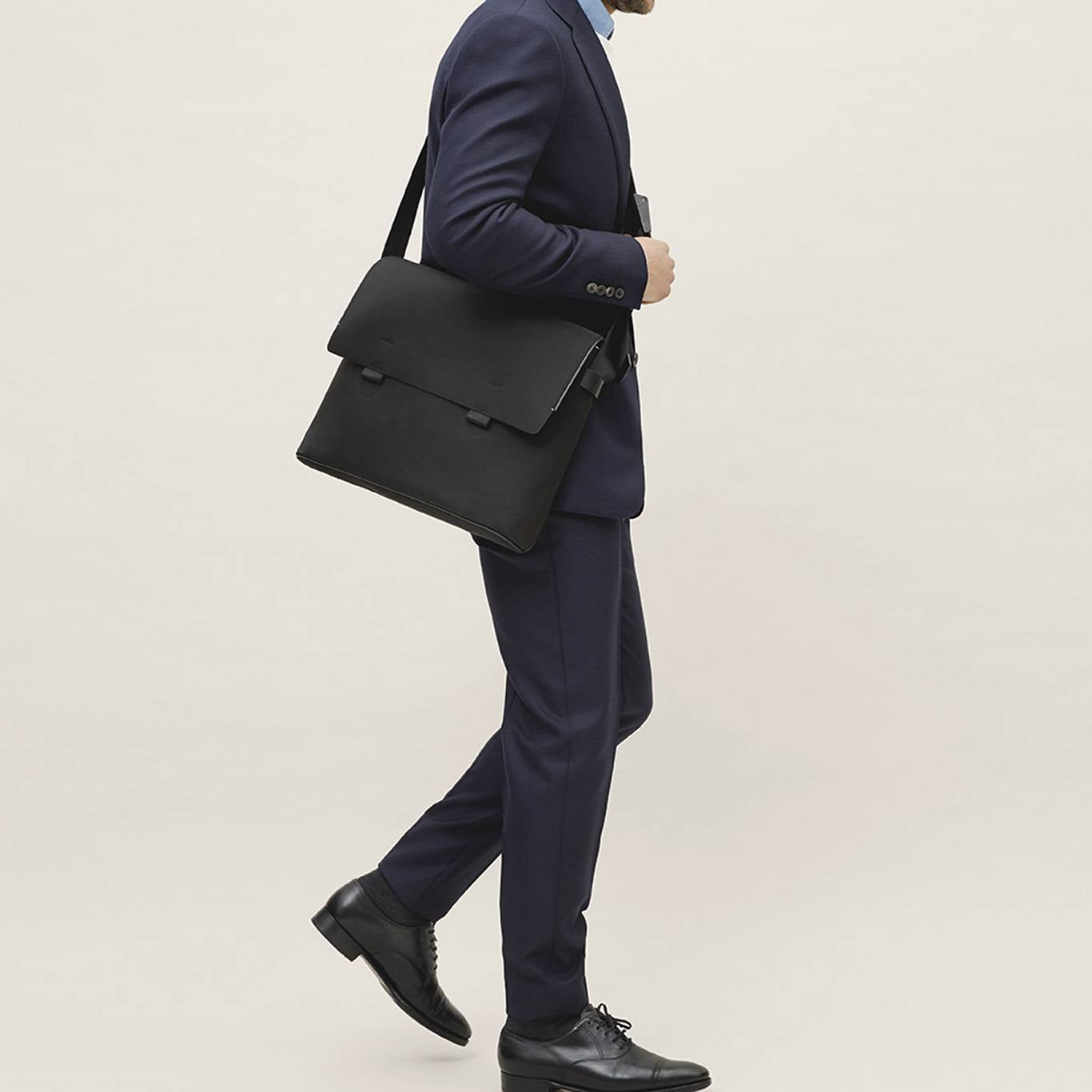 Navy blue suit paired with a black messenger bag