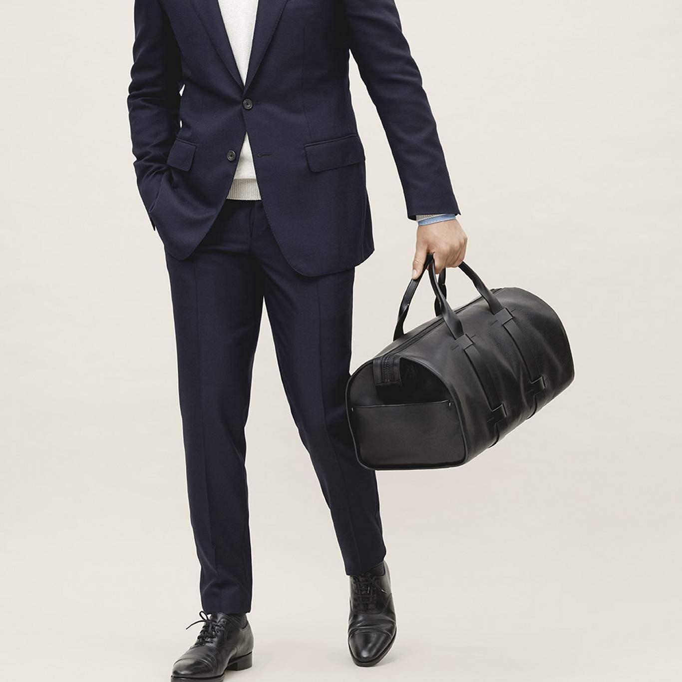 Navy suit and minimal men's black leather bag