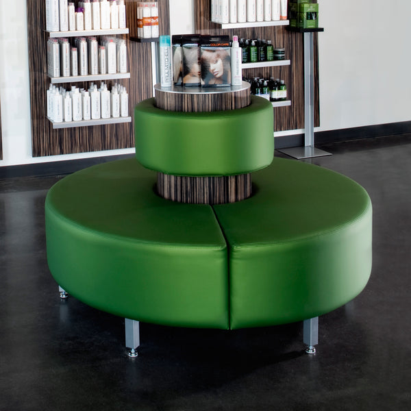 Concentric reception bench offers three hundred sixty degrees of style and function for you and your guests.  Shown in green synthetic leather with silver legs and a wood veneer center column.
