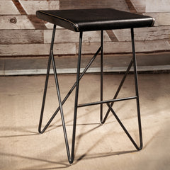 Saddle up to utility and beauty with Trestle stool, perfect behind your reception desk or at your make up counter. It's fabricated in a black iron rod frame, waxed finish. Topped with an upholstered seat cushion sewn with a large saddle stitch.