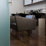 Detailed picture of Facet Wash backwash unit including brown upholstered chair with black legs and black shampoo bowls.