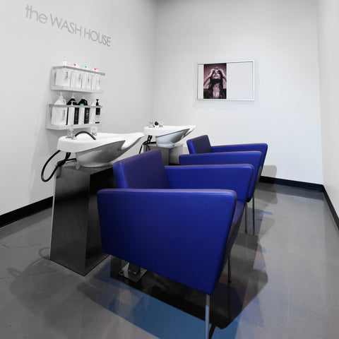 Facet Wash is a clean modern shampoo station for your salon.  Two wash stations with chairs shown in blue synthetic leather with silver legs and white shampoo sinks.