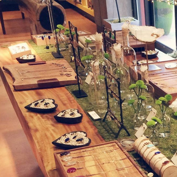 Shot of pieces of jewelry on a long wooden table with moss centerpiece at New Twist in Eugene OR