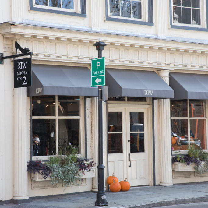 An exterior shot of white building with grey awnings. RTW in Charleston