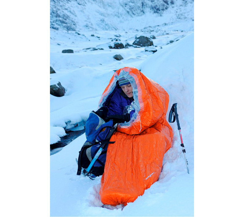 An orange Blizzard Survival Bag in use in extreme cold weather.