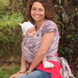 Caregiver smiling look at camera while front carrying baby. BabyMonkey, Shade Collection Wild Horse Ice woven wrap, baby carrier for babywearing.
