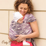 Caregiver looking down at baby while front wrapping, leaning against wall. BabyMonkey, Shade Collection Wild Horse Ice woven wrap, baby carrier for babywearing.