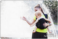 Caregiver doing front carry by water. Natibaby Nevada woven wrap, baby carrier. Marsupial Mamas