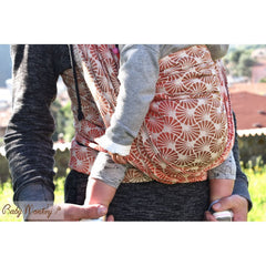 Caregiver holding onto child feet being carried in a front carry. BabyMonkey: Shade Collection Papyrus Wood woven wrap, baby carrier.