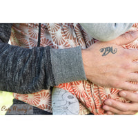 Arms and hand visible of caregiver holding onto child.  BabyMonkey: Shade Collection Papyrus Wood woven wrap, baby carrier.