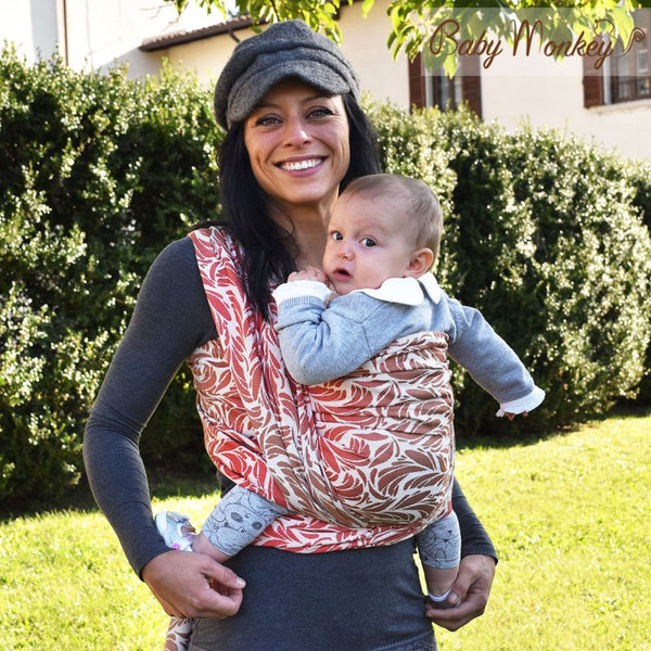 Caregiver carrying child in a front carry. BabyMonkey: Shade Collection Plumage Wood woven wrap, baby carrier.