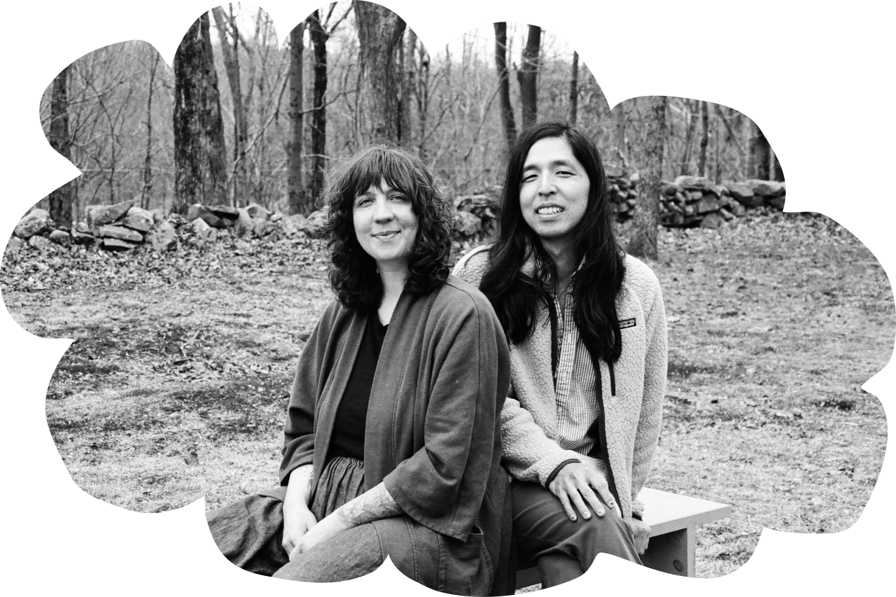 Black and white photo of Meow Meow Tweet's Founders: Tara, a white person with medium-length curly hair, a linen jacket, and super cool floral tattoos on their forearm (left) and Jeff, an Asian-identifying person with long, straight hair, a really cool fleece, and nail polish (right) sitting on a wooden bench near a tree line. The photo is cut out in the shape of a cloud