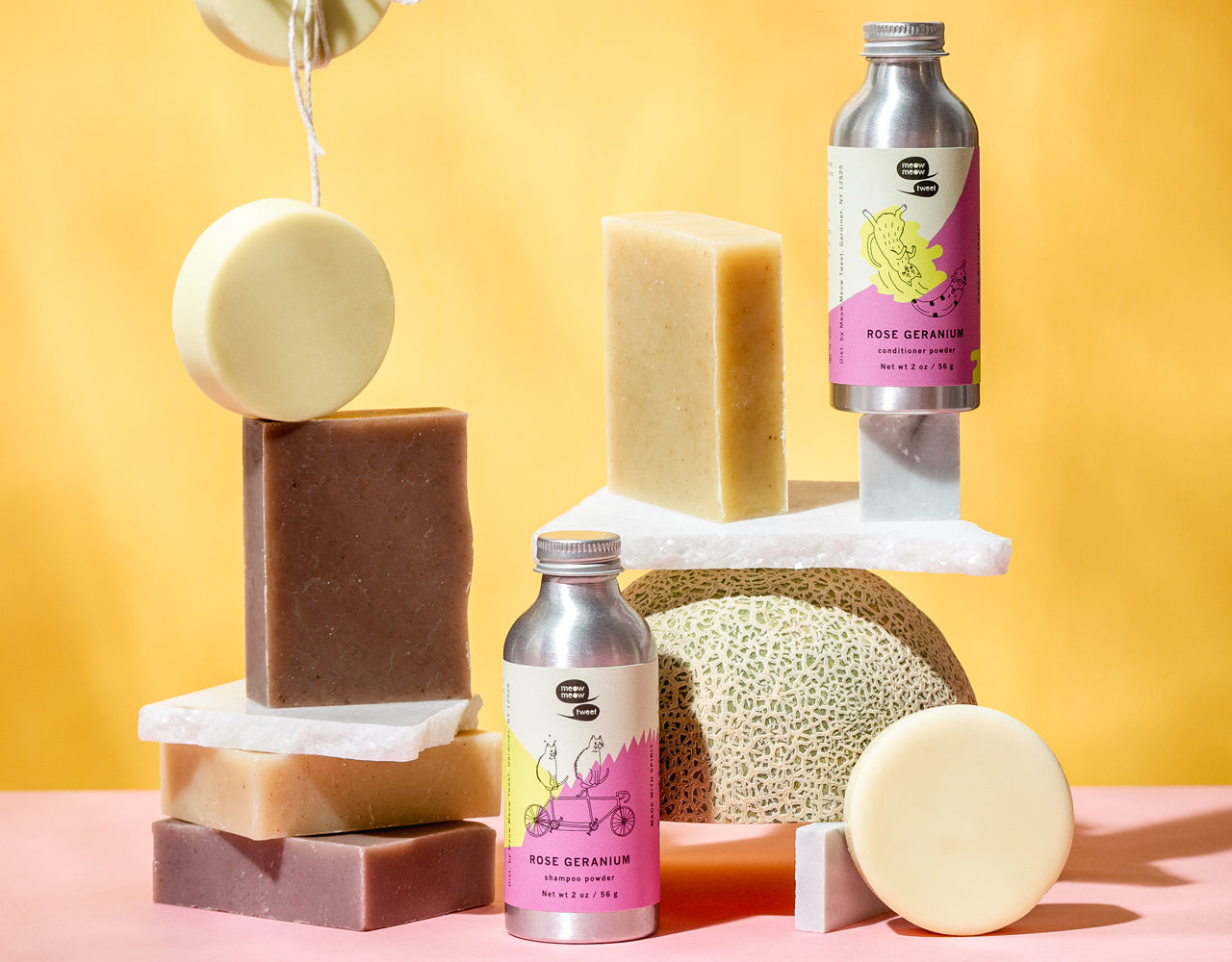 our hair bars and powders stacked in varying levels with slabs of marble and a cantaloupe. the background is peach and the ground is pink.