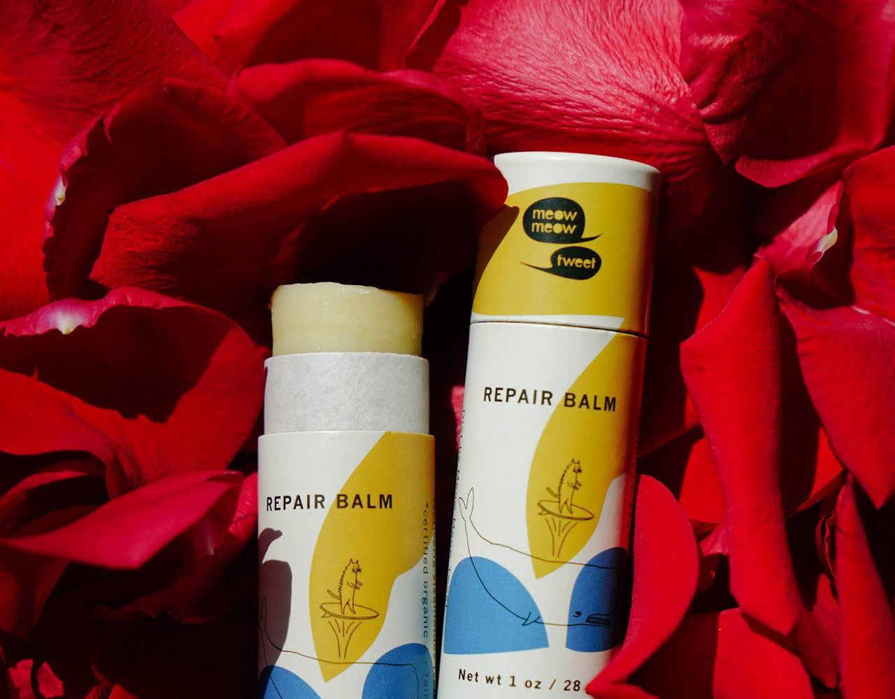Open stick of repair balm against a background of red rose petals