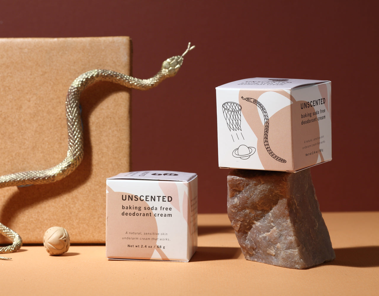 Two Meow Meow Tweet Unscented Deodorant boxes in a scene with a cork block, gold plastic snake, round clay charm with a carved heart, and brown granite; on a sand-colored surface and against a rust-colored background