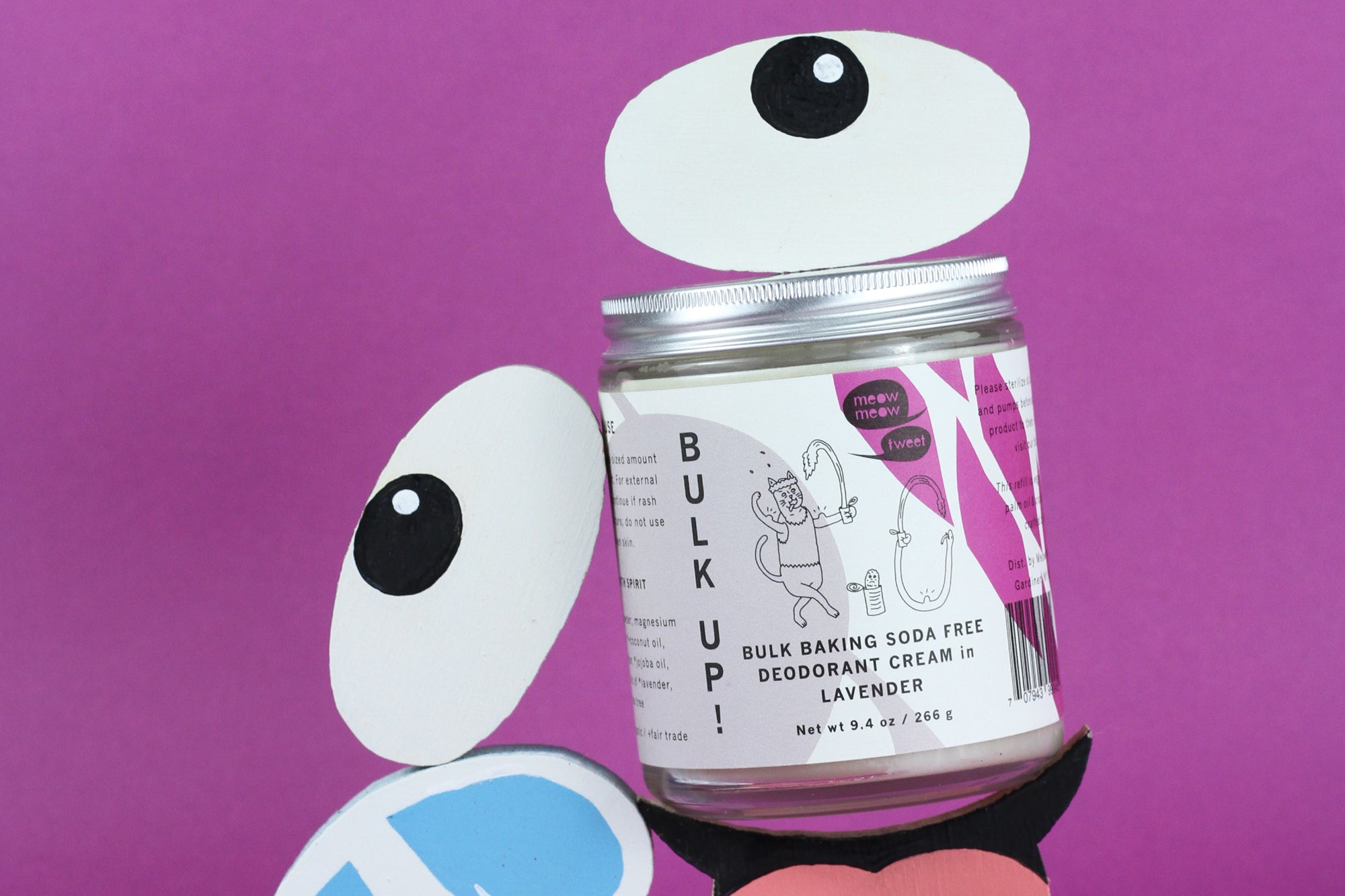 a bulk deodorant sitting with wooden carved and painted emojis of googley eyes