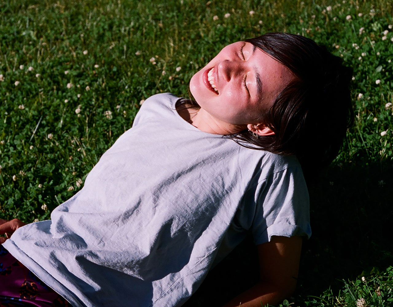 Person with black hair and a white t-shirt lying on the their back on the grass in full sun