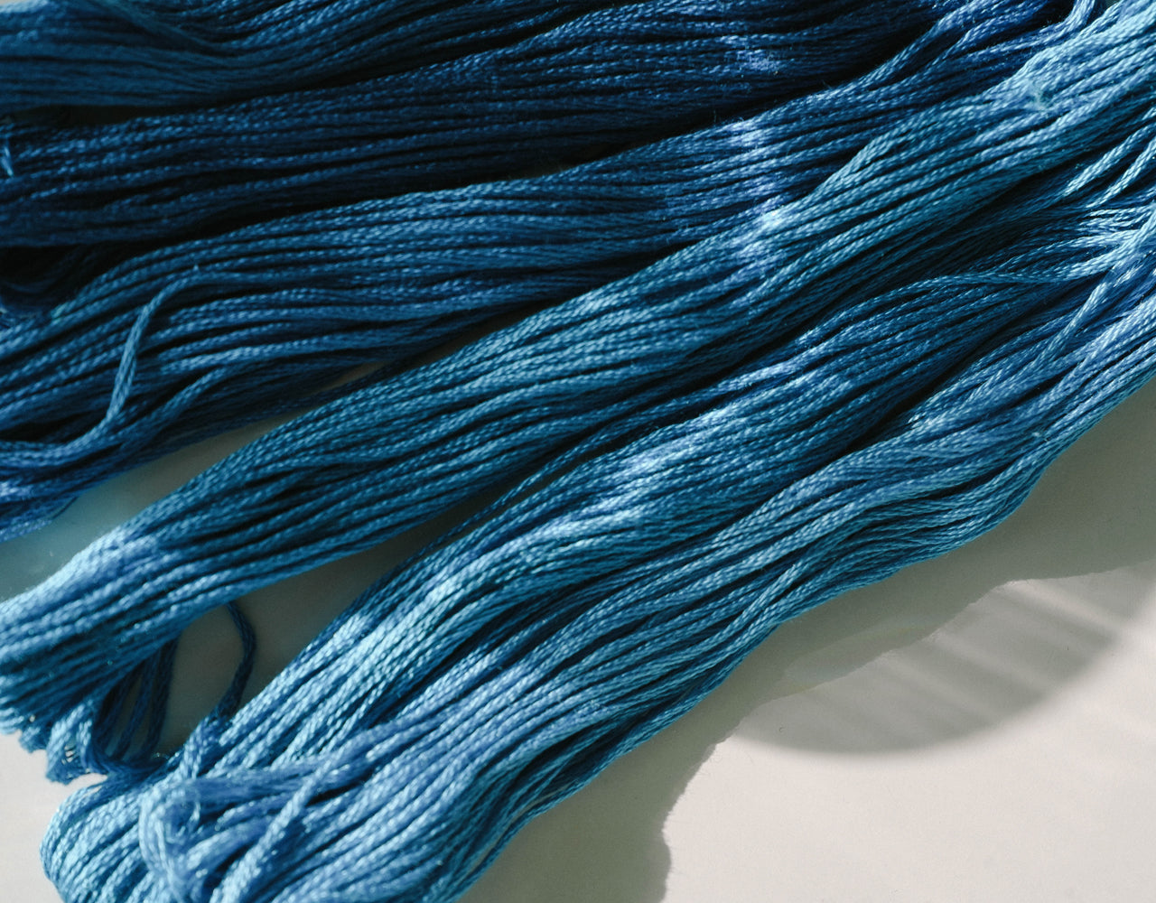 Close-up of bunches of indigo-colored cotton thread with spots of light shining on it