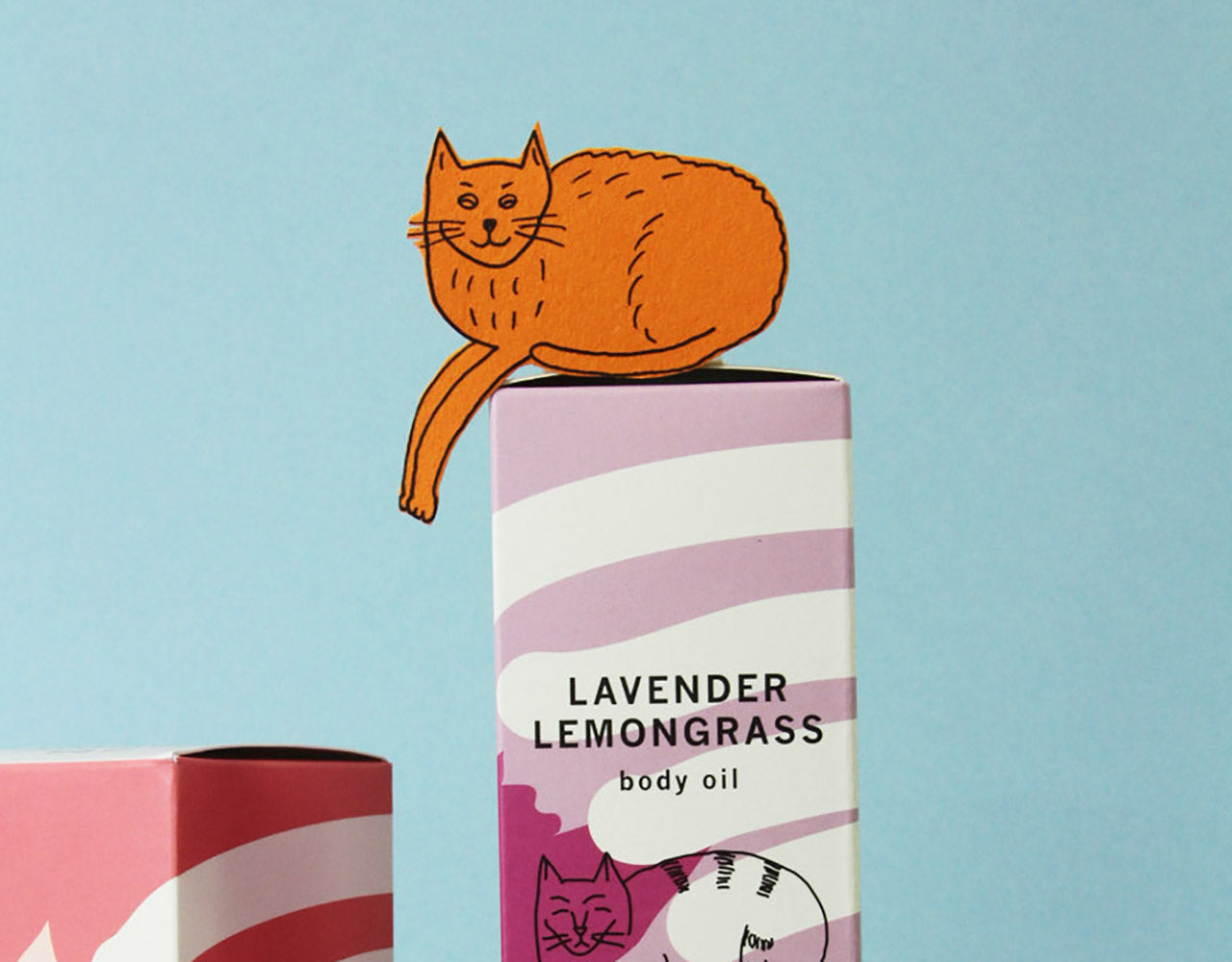 hand-drawn orange paper cat cutout on top of a box of Meow Meow Tweet Lavender Lemongrass body oil against a light blue background
