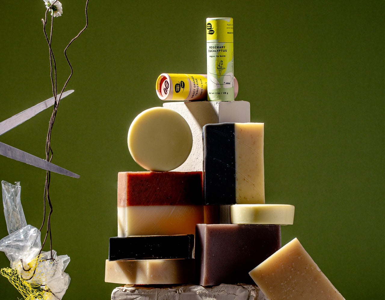 our soaps and lip balms stand in a tower against a pine backdrop, with a pair of scissors on the left open and ready to cut the stem of a flower that's connected to plastic waste