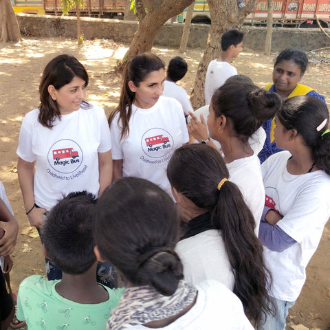 Amita Bhalla and other Magic Bus volunteers talking to women and children in India