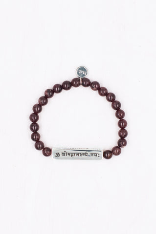 This beautiful combination of silver sanskrit and garnet gemstones honours Lakshmi.