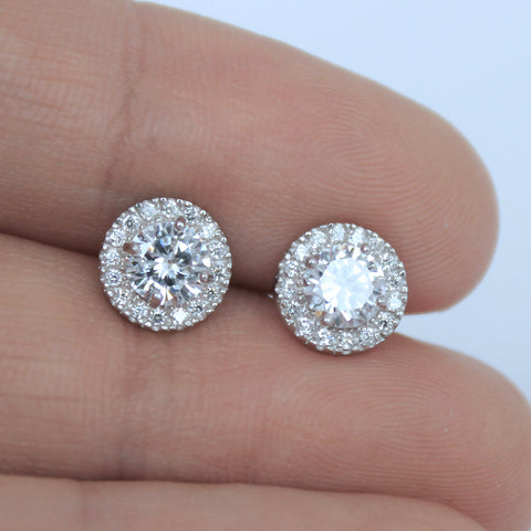 Cubic zirconia halo earrings between two fingers