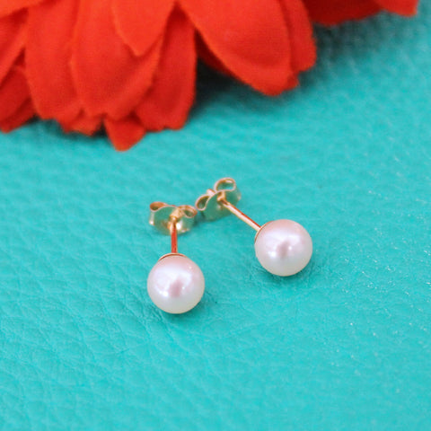 Pearl earrings on blue leather background