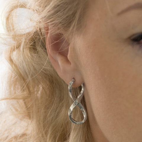 Woman wearing white gold infinity hoop earrings