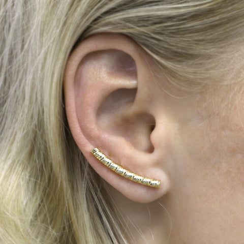 woman wearing gold sparkly climber earrings