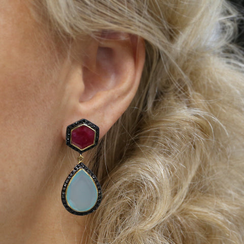 woman wearing large blue and red ruby gemstone earrings