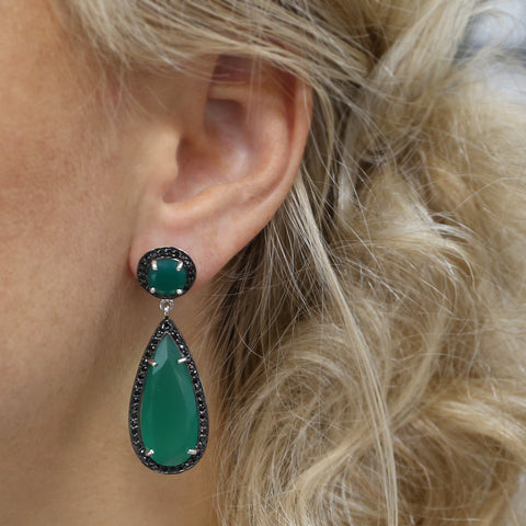 woman wearing large green and black gemstone teardrop earrings