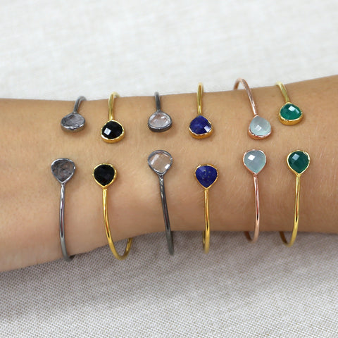 Woman wearing many gemstone cuff bracelets