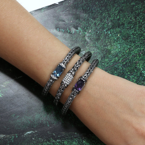 Woman wearing three black silver gemstone woven bracelets
