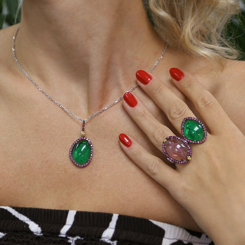 Woman wearing green and pink cameo rings and a green cameo necklace
