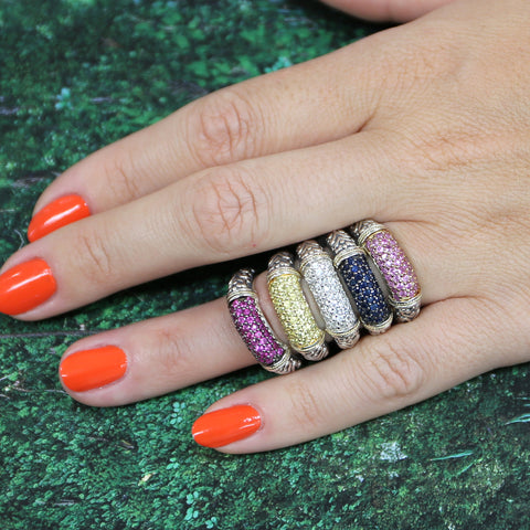 Woman wearing orange nail polish and many gemstone rings