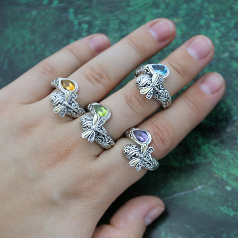 Woman wearing many gemstone dragonfly rings