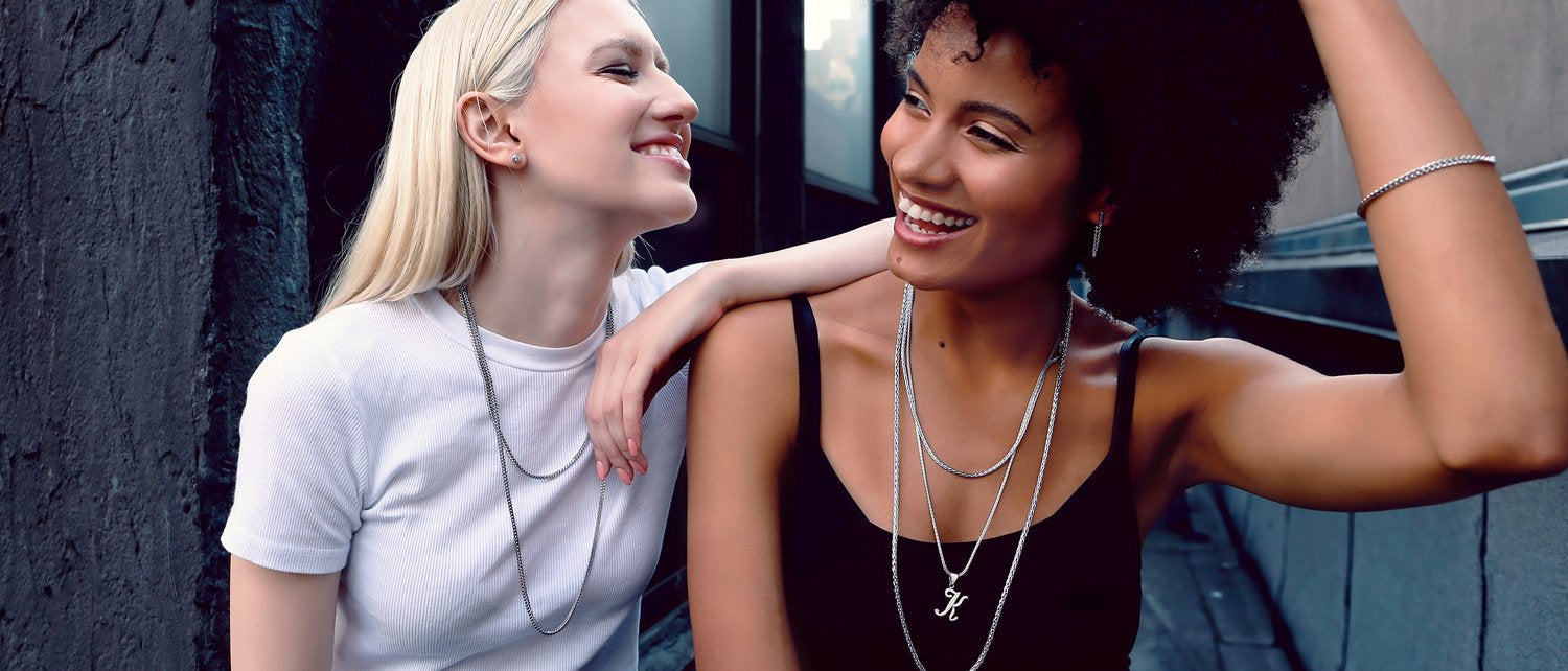 Two women sitting and laughing together while wearing sterling silver necklaces