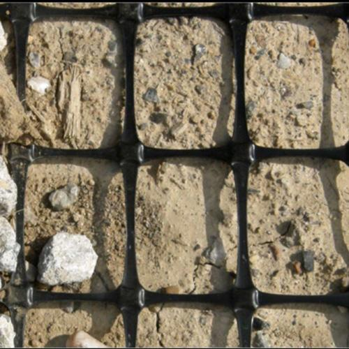 GBX-12 Biaxial Geogrid on the ground with dirt and rocks