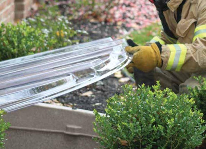 Firefighter lifting up the egress window well cover