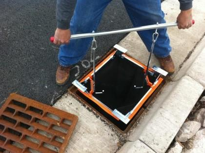 Flexstorm inlet filter being lifted out of a grate with a lifting tool