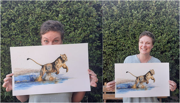 artist with photo realistic watercolor piece of lioness running through water
