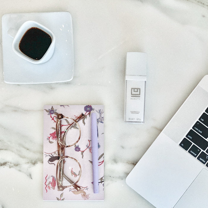U Beauty Blog | Tips for Staying Sane While Staying Home | image of a cup of coffee, glasses and pen on a notebook, Ubeauty and a computer on a countertop