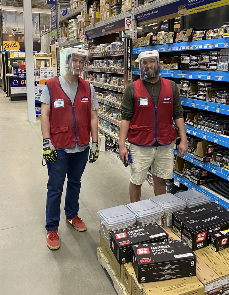 Two male Lowes employees wearing face shields to protect themsevles from coronavirus during the pandemic.