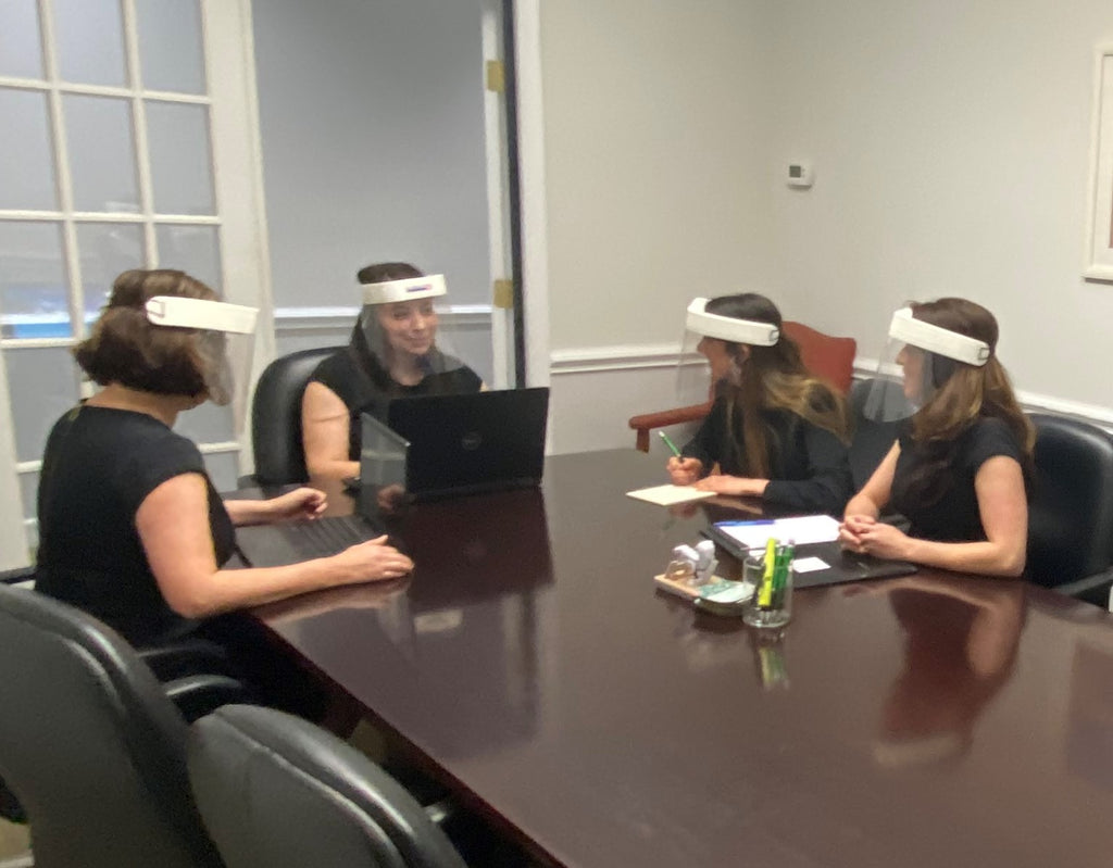 Four women sit in a meeting wearing face shields for protection.